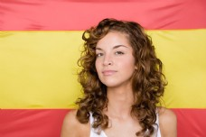 西班牙国旗背景前的卷发美女图片