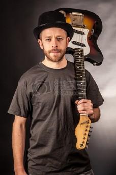 男子在黑色T恤控股电吉他倒挂