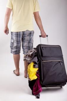 拉一堆衣服旅游的男人图片