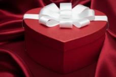 红色爱心礼盒与绸布背景图片