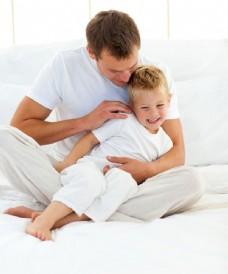 坐在床上的外国父子图片